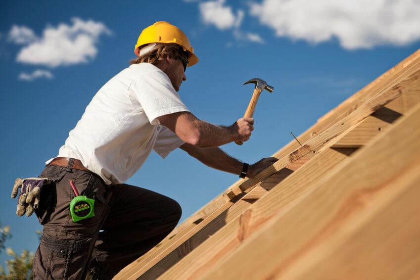 Un couvreur professionnel travaille sur une charpente en bois.